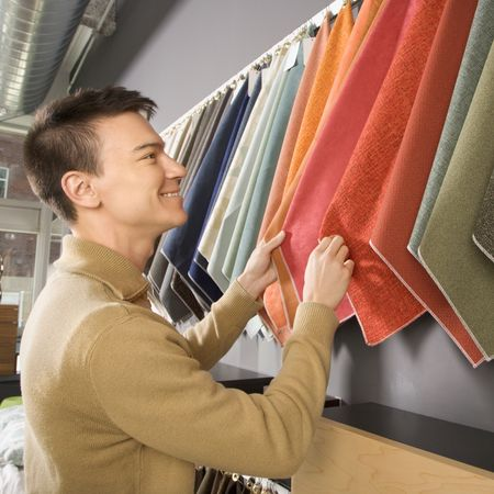 Asian male looking at fabric swatches in retail store. Stock Photo - 1874769