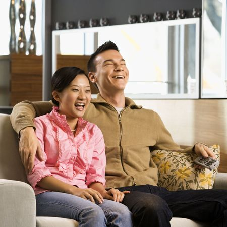 Asian couple laughing while watching television. photo