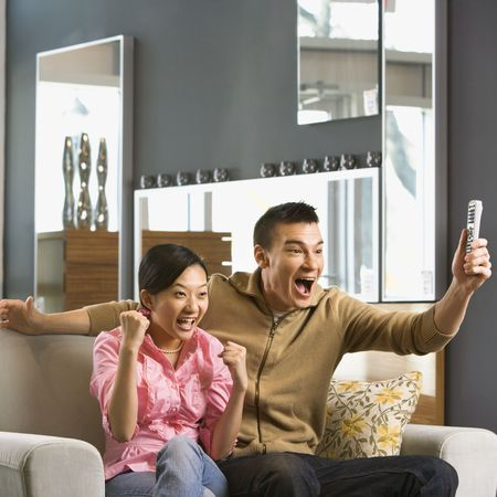couple watching tv: Asian couple cheering while watching television.