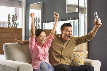 Asian couple cheering while watching television. photo