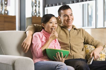 snacking: Asian couple watching television. Stock Photo