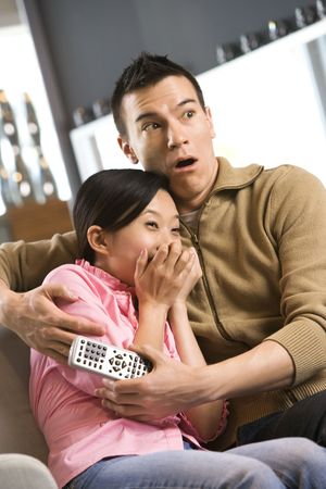 Asian female with scared expression while Asian male comforts her. photo