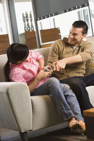 Asian couple fighting over remote to TV. photo