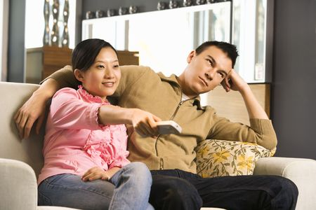 Asian female pointing remote while Asian male looks annoyed. Stock Photo - 1874702