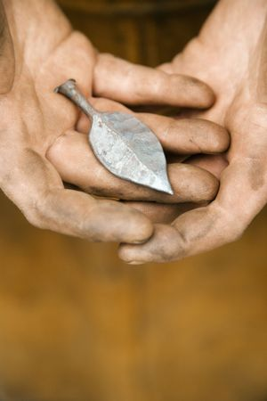 Dirty caucasian male metalmiths hands holding metal leaf. photo