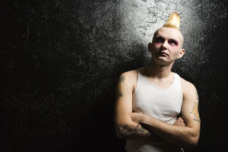 Portrait of mid-adult Caucasian male punk with crossed arms.
