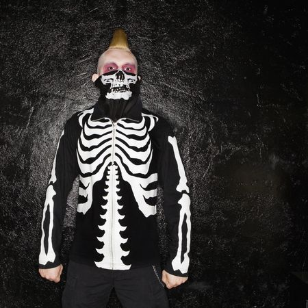 Mid-adult Caucasian male punk wearing skeleton sweatshirt and skeleton bandanna. Stock Photo