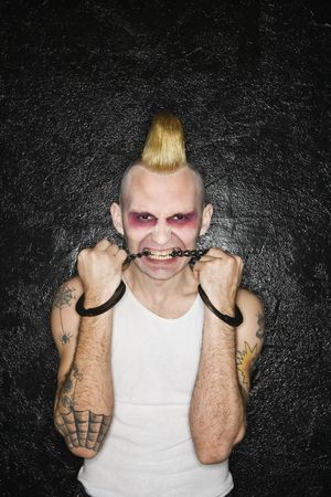 detained: Mid-adult Caucasian male punk biting handcuffs. Stock Photo