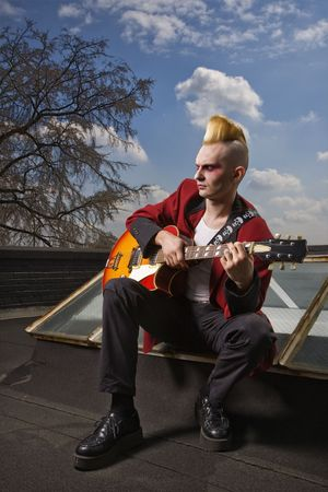 skylight: Portrait of a mid-adult Caucasian male punk  sitting on a skylight playing guitar.