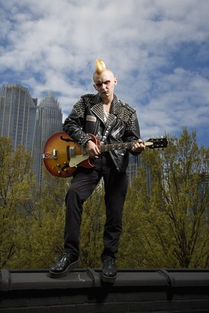 Portrait of mid-adult Caucasian male punk holding guitar with skyline in background. Stock Photo - 1874665