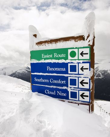 on cloud nine: Snow covered sign with arrows to slopes.