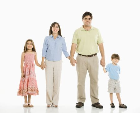 Hispanic family of four standing against white background holding hands.