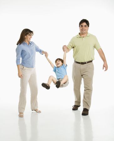 Hispanic mother and father swinging son against white background. photo