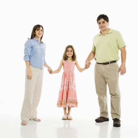 Hispanic parents and daughter holding hands standing against white background. photo