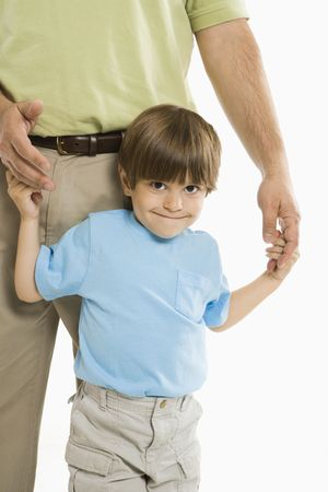 Boy holding onto fathers hands standing against white background. photo