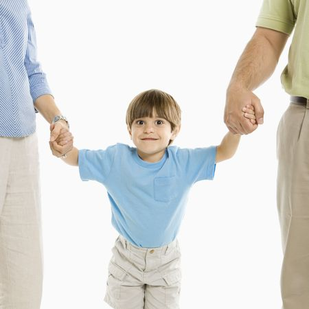 Boy holding hands with parents standing against white background. photo