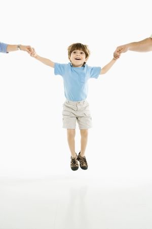 Boy jumping into air holding hands with parents against white background. photo