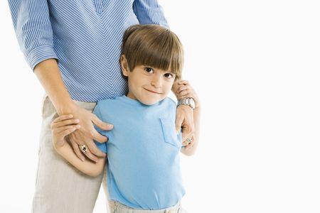 ni�o parado: Boy permanente con la madre contra el fondo blanco.
