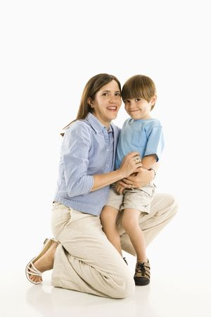 Mother kneeling down holding son against white background. Stock Photo