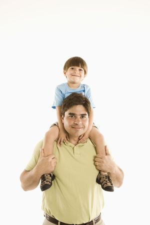 Father holding son on shoulders standing against white background. Stock Photo