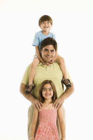 Father with son and daughter standing against white background. photo