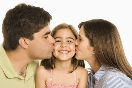 Mother and father kissing smiling daughter on cheek. photo