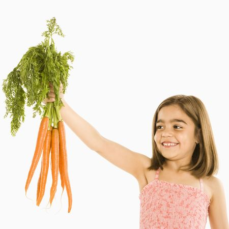 Smiling girl holding bunch of carrots against white background. Stock Photo - 1874484