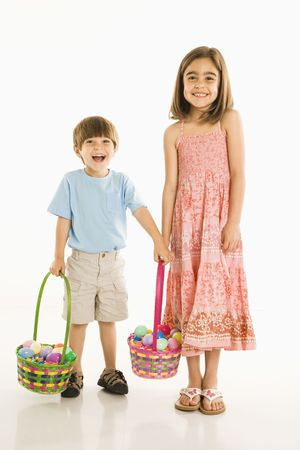 Smiling girl and boy standing with Easter baskets against white background. Stock Photo - 1874559