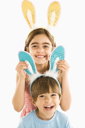 Portrait of boy and girl wearing rabbit ears smiling. photo