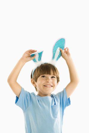 Portrait of boy wearing rabbit ears smiling. photo
