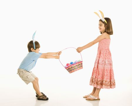 Boy and girl wearing bunny ears fighting over Easter basket.