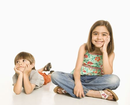 Girl sitting smiling next to boy lying on stomach looking bored. Stock Photo - 1874523