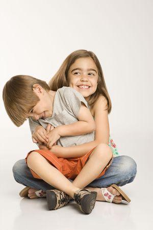 Boy sitting on girl's lap smiling against white background. Stock Photo - 1874526