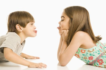 woman profile: Portrait of girl and boy lying looking at eachother sticking out tongues.
