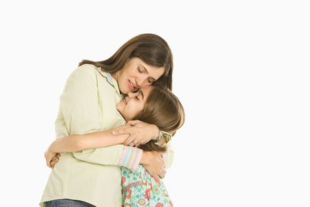 Mother and daughter embracing standing against white background. photo