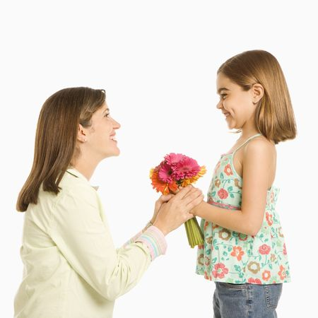 Girl giving bouquet of flowers to mother. photo