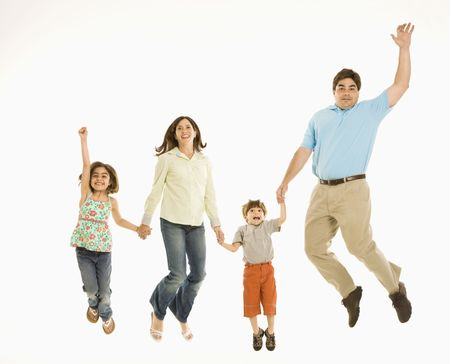 Family jumping and smiling while holding hands.