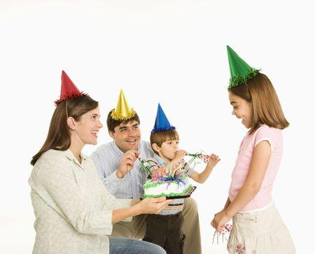Family celebrating girls birthday with cake. photo