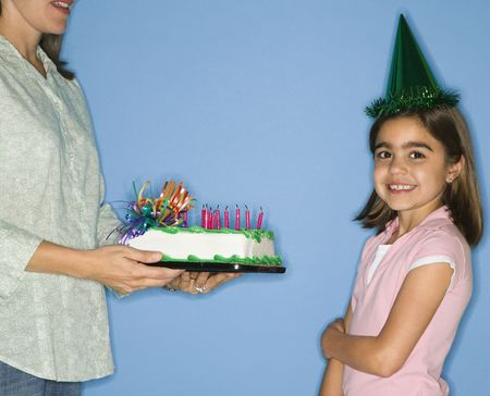 Girl wearing party hat with mother holding birthday cake. photo