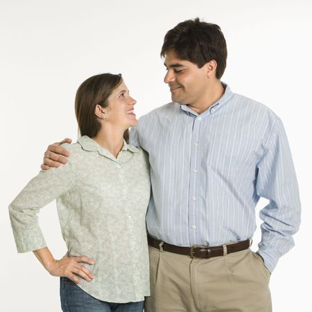 eachother: Couple standing smiling at eachother against white background. Stock Photo