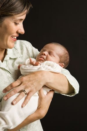 Mother smiling holding baby against black background. photo
