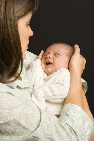 boy crying: Mother smiling holding baby against black background.