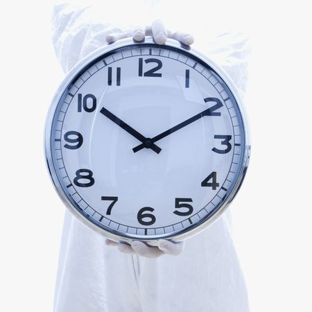 Man in biohazard suit holding out clock standing against white background. Stock Photo - 1906319