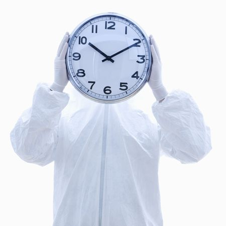 Man in biohazard suit holding clock in front of face standing against white background. photo
