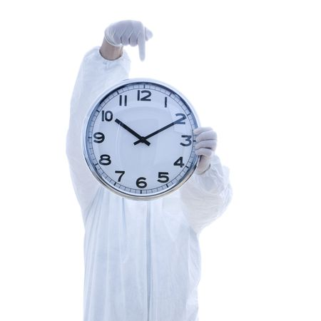 Man in biohazard suit holding clock in front of face pointing to clock with finger standing against white background. Stock Photo - 1906274