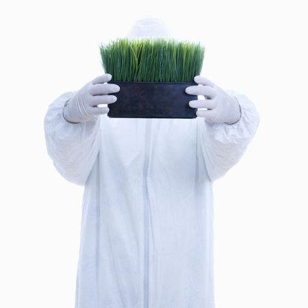 Man in biohazard suit holding pot of grass in front of face standing against white background. Stock Photo - 1906279