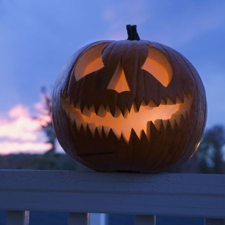 Carved Halloween pumpkin perched on porch railing. Stock Photo - 1906320