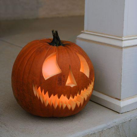 Carved Halloween pumpkin sitting on doorstep. Stock Photo - 1906700