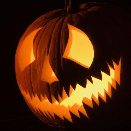 Carved Halloween pumpkin glowing in the dark. Stock Photo - 1906582