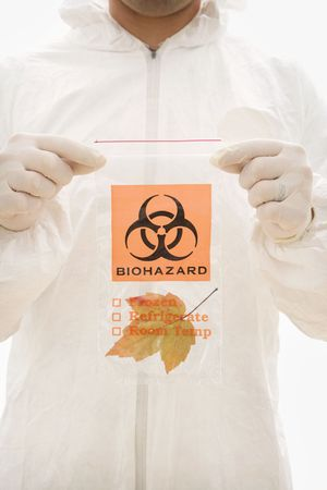 Man in biohazard suit and rubber gloves holding plastic biohazard bag containing orange Maple leaf. Stock Photo - 1906326
